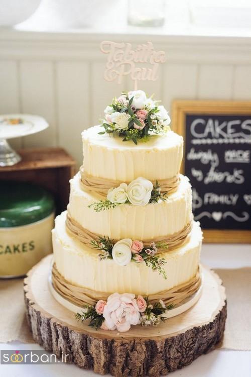 کیک عروسی با روکش خامه با گل طبیعی صورتی و زرد