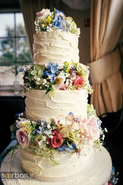 کیک عروسی با روکش خامه و گل های طبیعی رنگارنگ و شکوفه